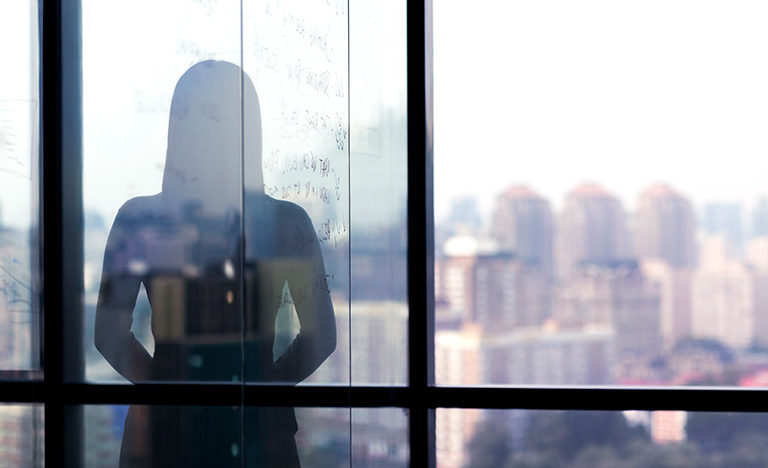 Girl leaning against window, silhouetted against the city.