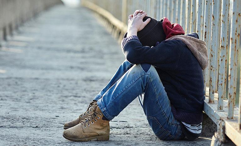 A sad teenage boy sitting on the ground outside.