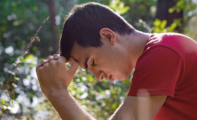 A teenage boy sitting in a garden looking stressed out.