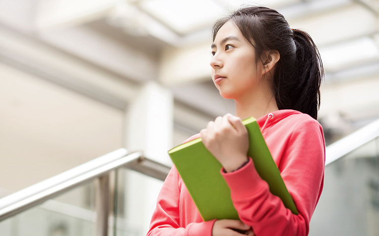 Girl in pink shirt walking down steps holding a green textbook
