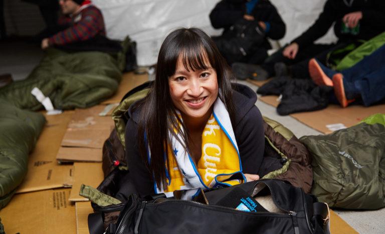 Happy woman sitting on a sleeping bag.