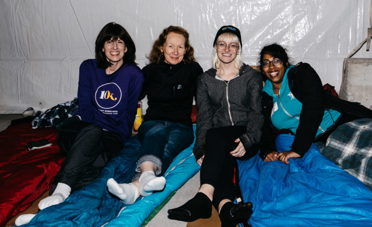 Group of happy women sitting on sleeping bags.