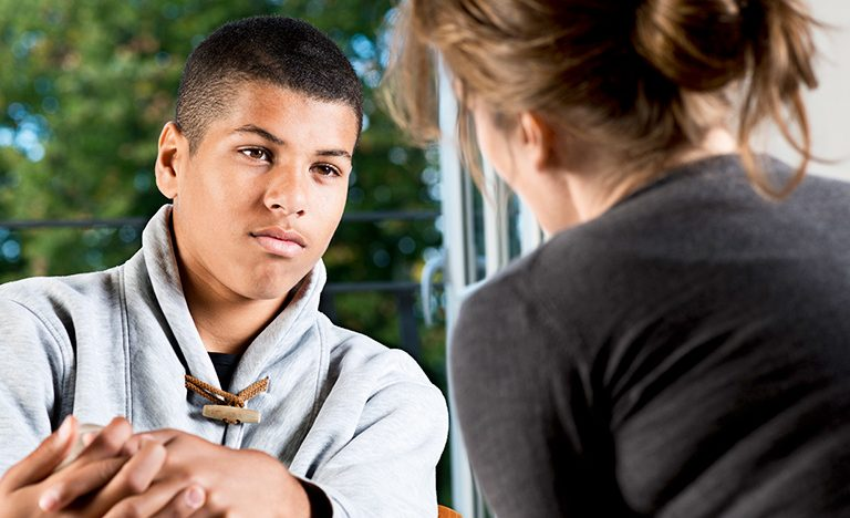 Teenage boy talking to an adult with a serious facial expression.