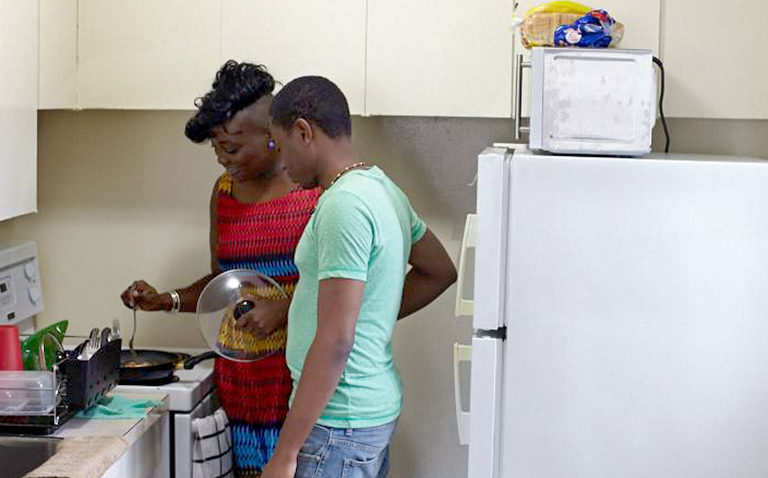 Two young people cooking in a kitchen.