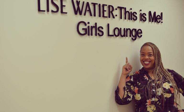 Covenant House volunteer Angela Grovey smiling and standing next to Lise Watier: This is Me! Girls Lounge sign