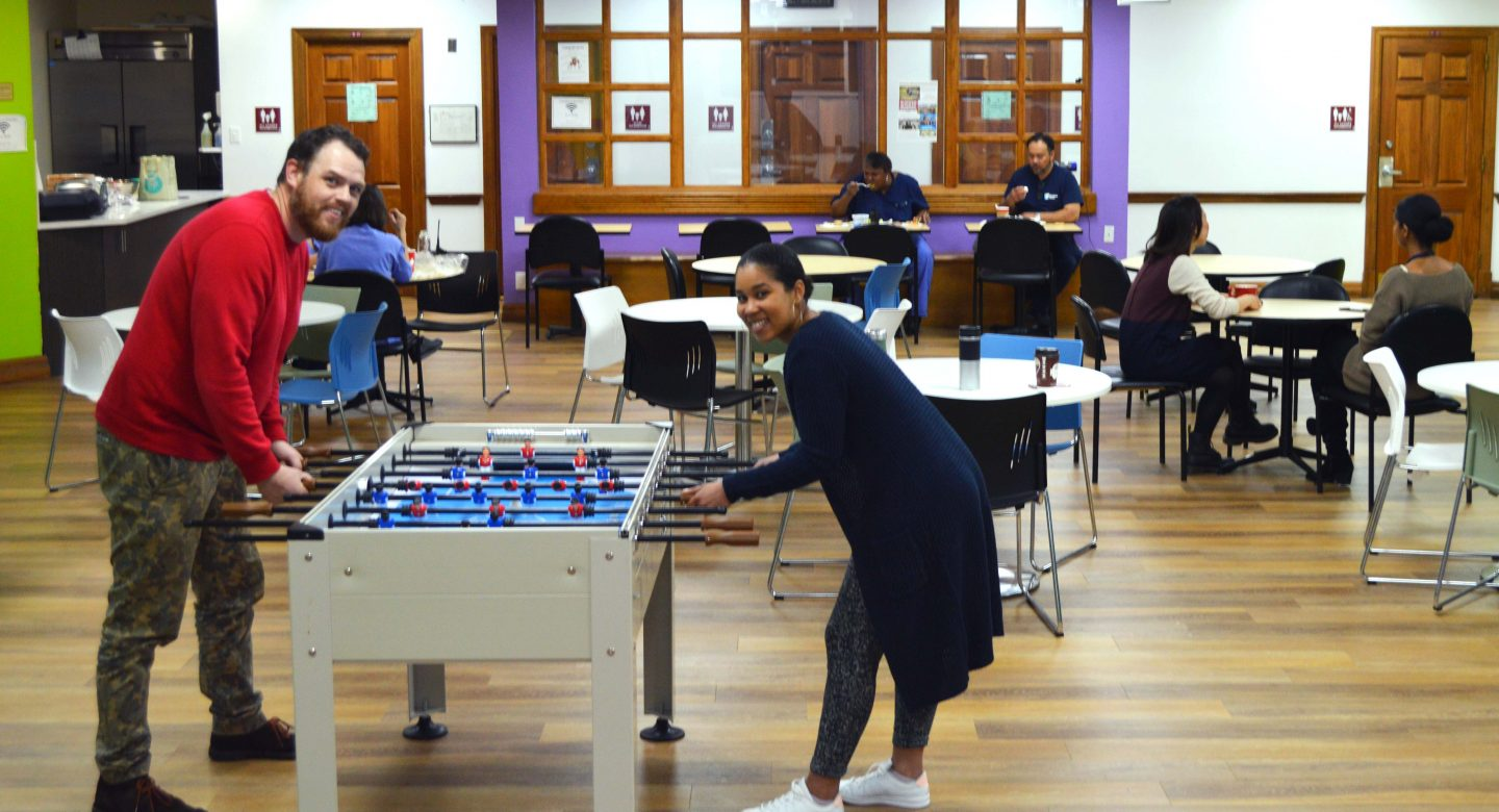 Two happy youth playing fooseball in open space.