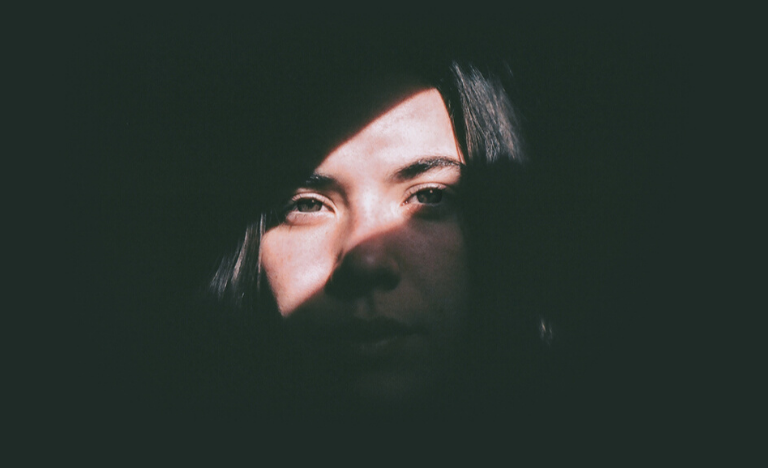 Young woman in darkness with her eyes illuminated by a strip of sunlight