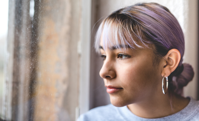 Young woman pensively looking out a window