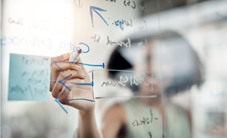 Woman formulating a plan on a glass board