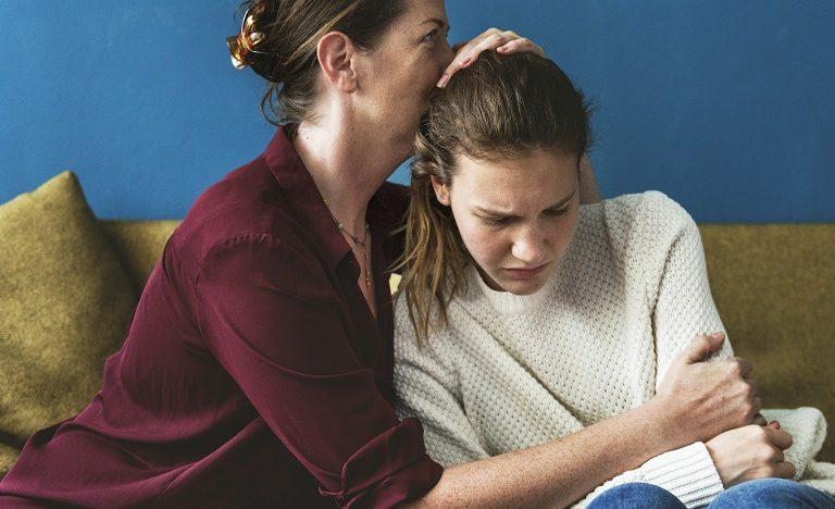 mother comforting her upset teen daughter