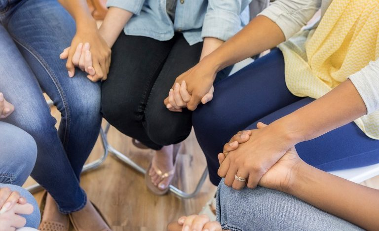 group of people sitting in a circle holding hands
