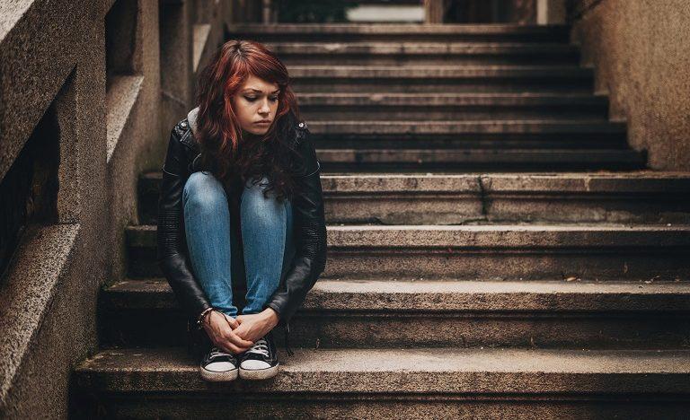 Sad teenage girl sitting on steps alone outside