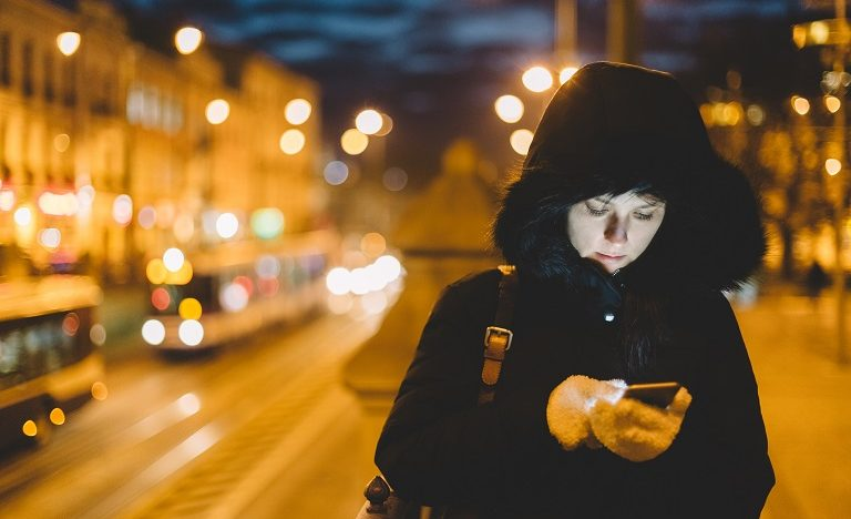 girl in the city wearing winter coat with head down sending a text message