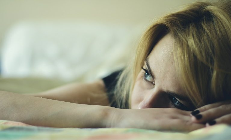 Young girl laying down in bed looking sad