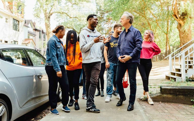 Board Chair, Kenneth Morell, walking down a street and chatting with several young people.