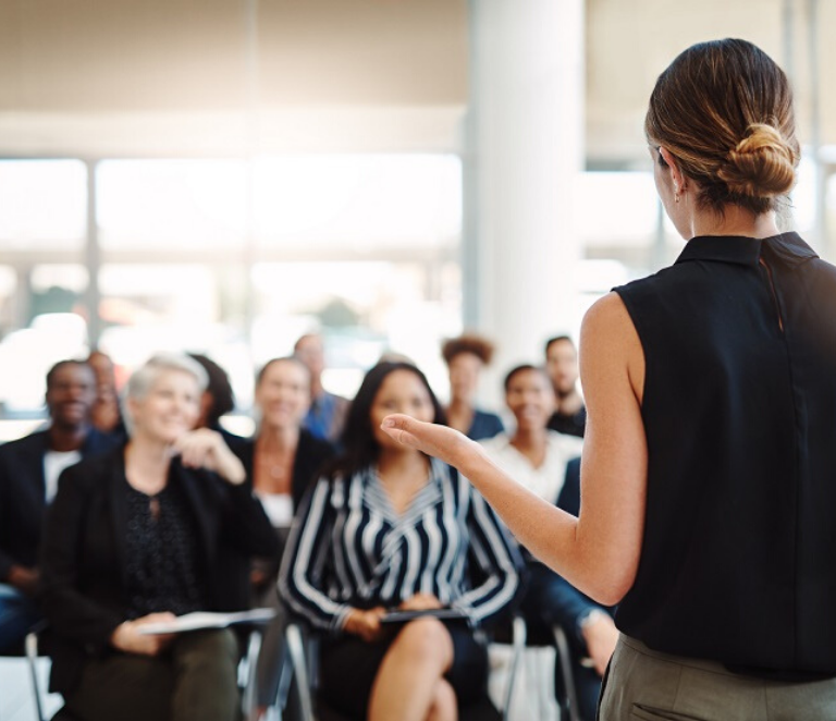 Female delivering a presentation to a group of people