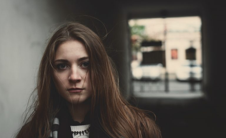 Young woman standing alone in an alleyway