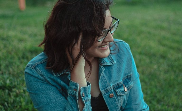 Young happy woman with glasses sitting on the grass.