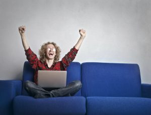 Woman sitting on couch cheering with excitement.