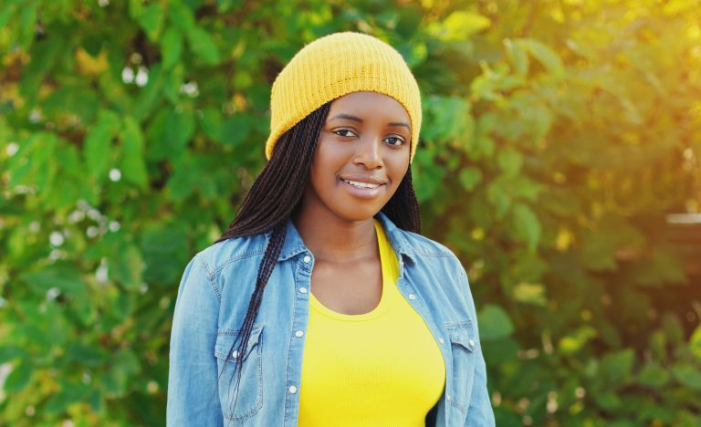 Young woman with braids standing outside wearing denim jacket and yellow hat